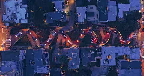Aerial drone pulling up of cars driving down the winding road of Lombard Street. In the background is the San Francisco Skyline with a view to the Bay Bridge