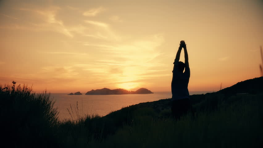Silhouette of active young man stretching doing yoga exercise on top of a mountain cliff on ponza island at sunset with the sea landscape on the background slow motion