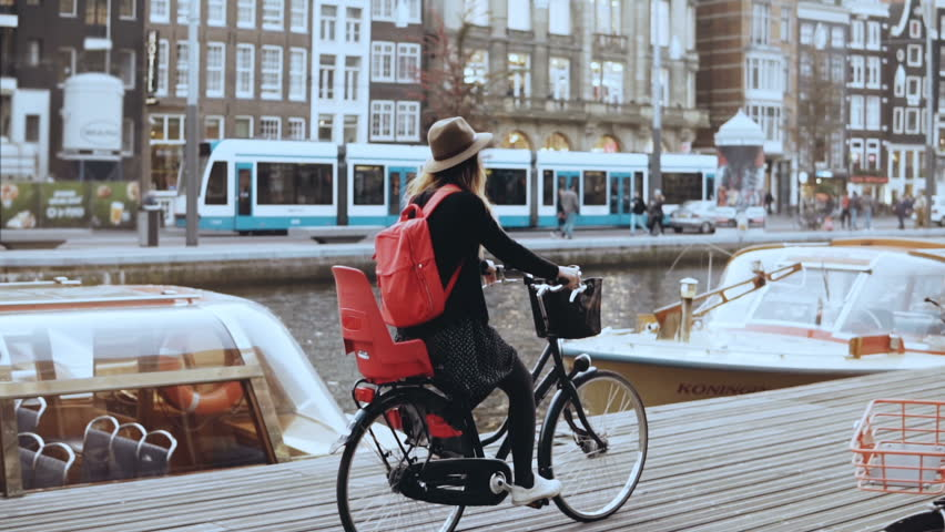 Student girl cycling bicycle along a river quay. Local commuter. Female in hat cruising on a city bike. Slow motion.