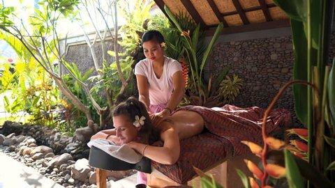 Caucasian woman having outdoor spa massage