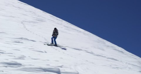 Man freeride skiing down snowy mount ridge in sunny day.Mountaineering ski activity. Skier people winter snow sport in alpine mountain outdoor.Front view.Slow motion 60p 4k video