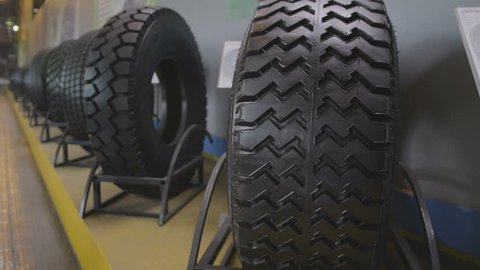 closeup camera moves along finished and exhibited tires with nameplates standing in metal racks