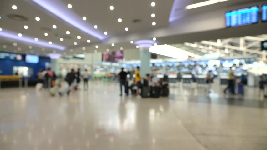 People walking inside large international airport in one of main terminal building for passengers. Blurred view