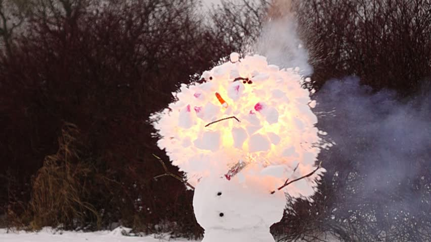 Super slow motion shot of petard explosion inside Snowman head. Fire burst inside top ball and snow fly apart around, destroying one snowball completely. Funny smiling face with pink cheeks blow up