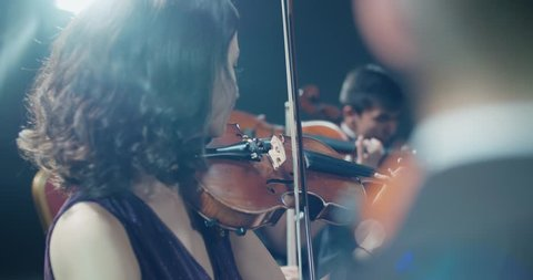 string quartet performs on stage, close-up of violin in work