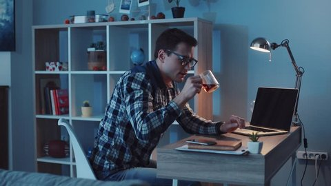 Attractive office worker working hard at his cabinet late at night, drinks tea and programming something on his computer. Workaholic, freelance position, making money. Slow motion, camera stabilizer