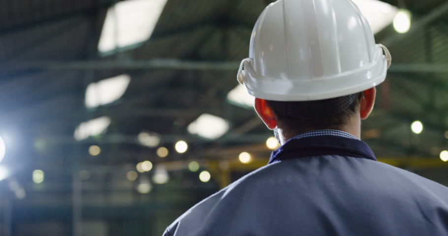 Close up of the factory worker in a helmet and glasses walking in a industrial facility. Working process on the background. Rear and from a side | Shutterstock HD Video #34775908