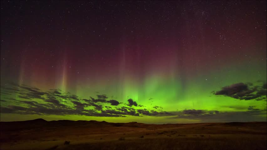 The northern lights suddenly brighten and fill the sky with color above Grasslands National Park, Saskatchewan.