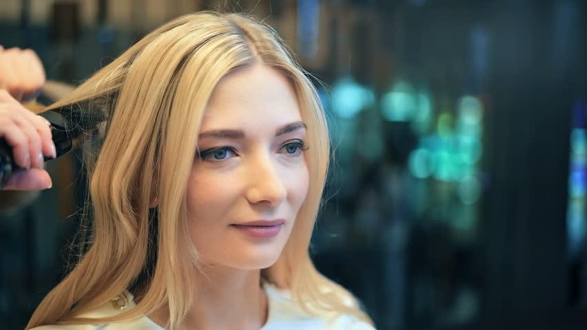 Professional hairdresser straightens model hair. Hair iron for hair straightening #34781908