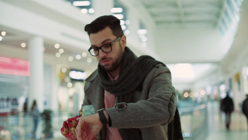 Close up of an attractive man wear coat with Christmas presents in a hurry at a mall smiling looking at a clock christmas family christmas decorations design tree love portrait slow motion