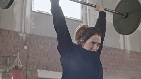 Gritty young woman in black hoodie doing overhead barbell raise while working out in gym