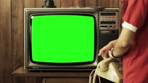 "Teenage Boy Talking on Old Phone and Turning Off Old Television with Green Screen. Ready to Replace Green Screen with Any Footage or Picture you Want. You Can Do it With ""Keying"" (Chroma Key) Effect."