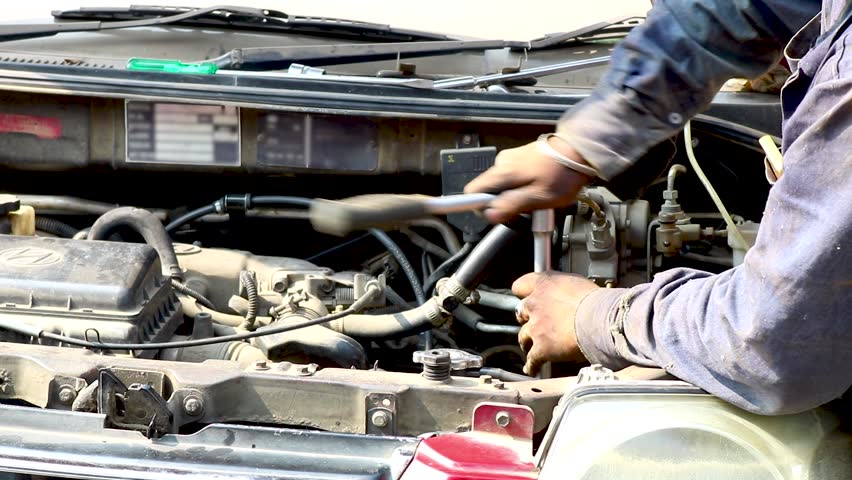auto mechanic tighten screw with spanner during automobile car maintenance at engine repair service station india