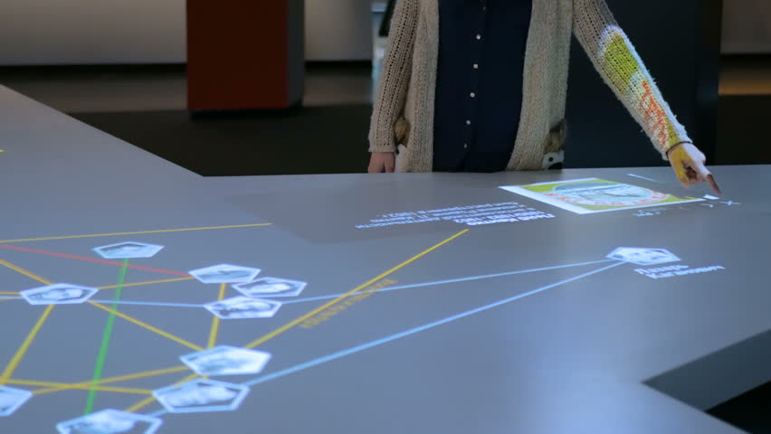 Woman using interactive touchscreen display stand with jewish victims of nazism at modern history museum. Education and technology concept