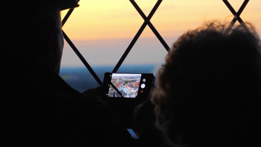 Senior couple taking a photo of cityscape of Lubeck from the observation deck