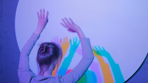 Interactive exposition in science museum. Colored shadows of dancing woman. Science, optical and physics concept