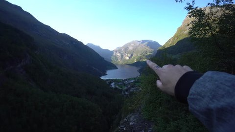 Pov shot with hand pointing to Geirangerfjord in Norway