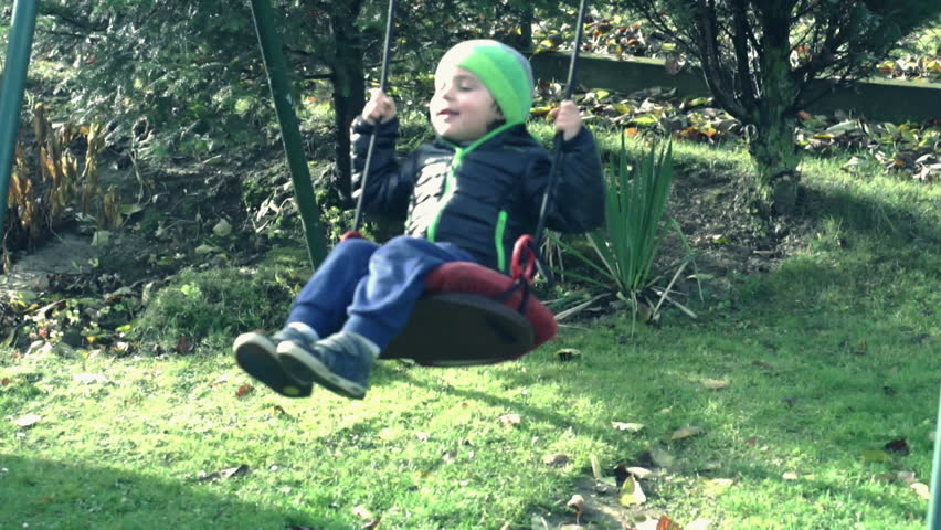 Little boy swinging in autumn park and smiling, slow motion shot at 120fps