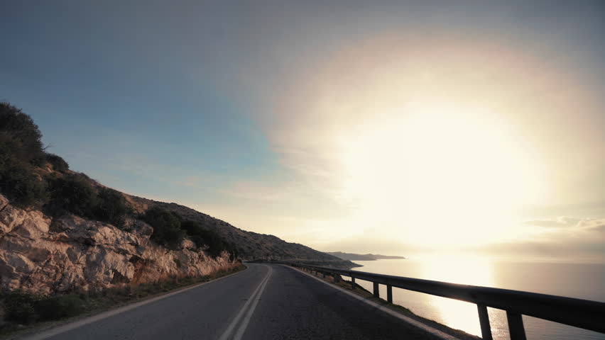 Coast to coast pov driving an a sunny winter morning.Driving point of view on the asphalt coastal road on a dramatic bright winter day at sunrise