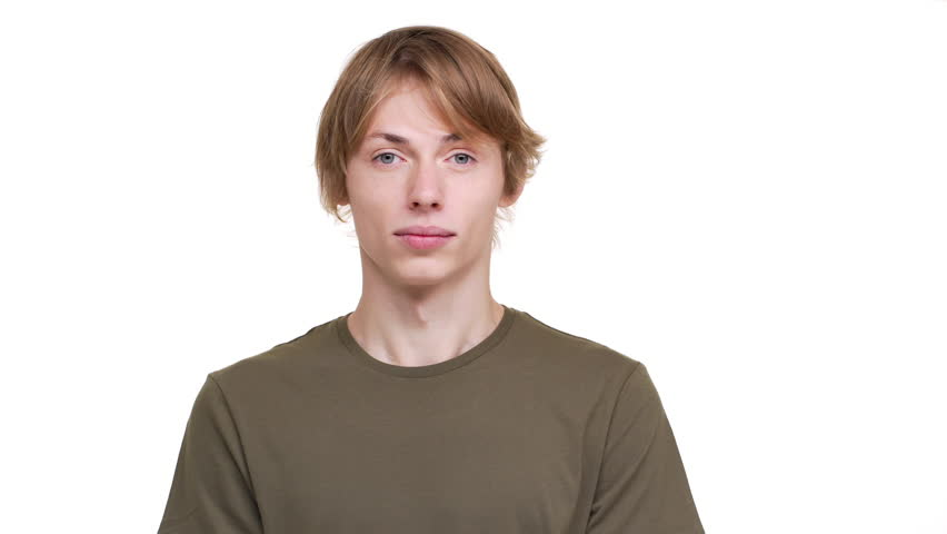 Portrait of young kind man in green t-shirt nodding in agreement looking on camera with smile meaning yes over white background. Concept of emotions