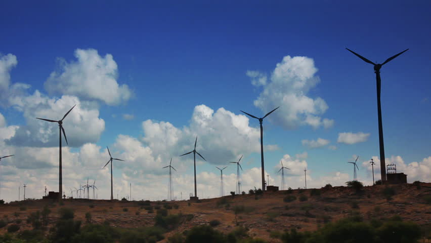 wind farm - turning windmills against timelapse clouds