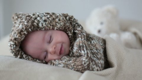 Little baby boy, dressed in cute knitted teddy bear overall, sleeping and smiling in his sleep
