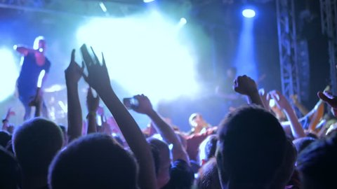 Silhouettes of people partying at rock concert in front of the stage. Strobing stage lighting