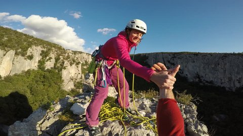 POV of happy climbers reaching the top of the mountain with amazing view.