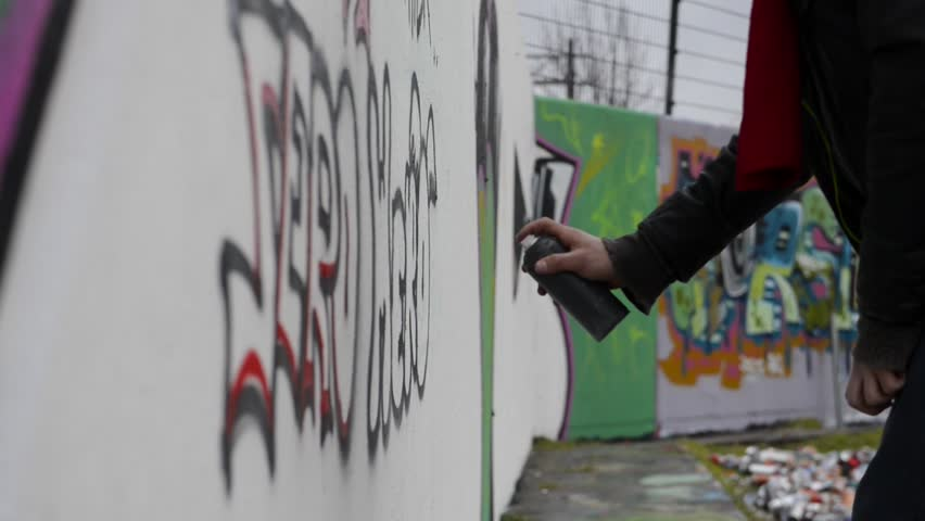 Man, using spray paint to create graffiti on a concrete wall