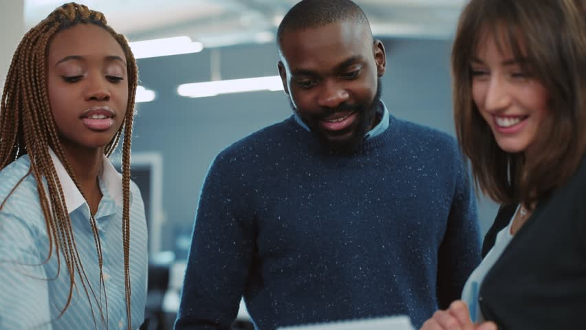 Young African man with beard demonstrating report to two colleagues. Young people working in modern office. Indoors. Close-up. | Shutterstock HD Video #34937725
