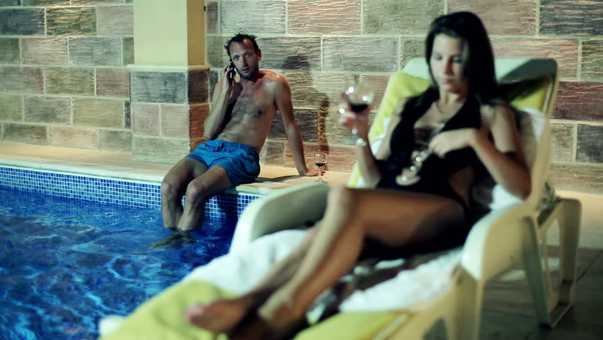 Young couple with cellphone sitting by the swimming pool at night  | Shutterstock HD Video #3493838