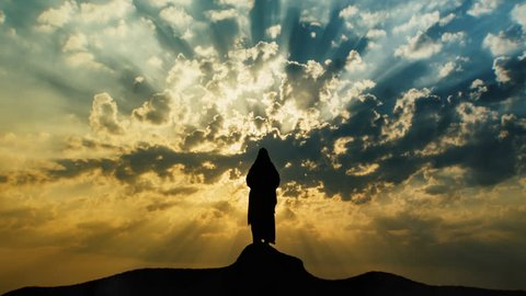Jesus silhouette standing on hill crest with sun and clouds behind Him. Representation of a prophet's dreams or vision.