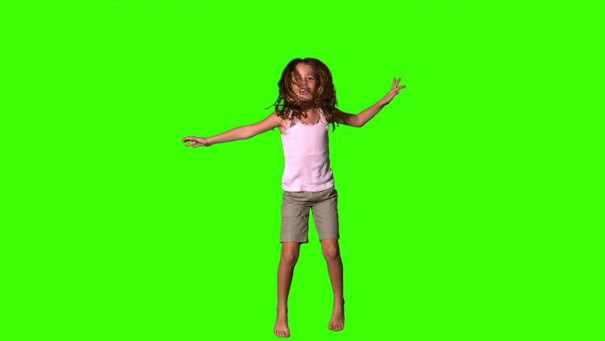Happy girl jumping up and down on green screen in slow motion #3497558