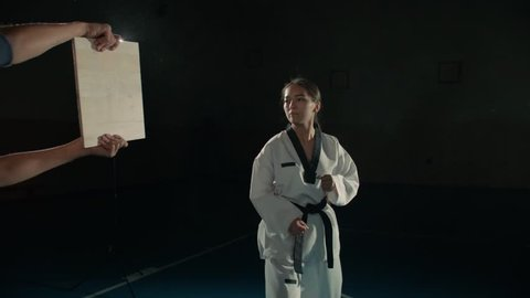 Asian beautiful girl fighter practicing to break the board with a blow to the hand, taekwondo in slow motion