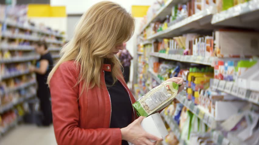 Young woman choosing food in grocery store, woman shopping in supermarket. 4k, background blur | Shutterstock HD Video #34998709