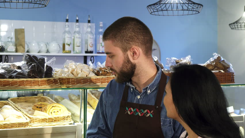 Professional male baker working at his shop helping his mature female customer  | Shutterstock HD Video #35009698