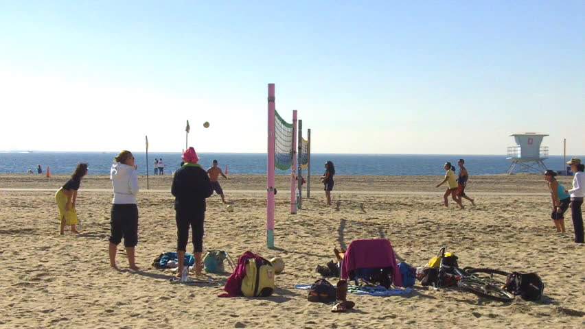 LONG BEACH, CA - February 23, 2013: A medium shot of young people playing a game of volleyball at the beach circa 2013 in Long Beach.