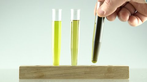 mans hand setting 3 glass tubes with extraction of cannabis oil and ethanol alcohol ,in first is unfiltered oil and ethanol, second is with filtered mix and third is with high concentration of oil