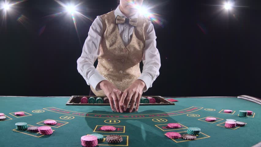 Casino croupier woman mixing the poker cards and performing trick with cards. Black background. Bright light. Slow motion