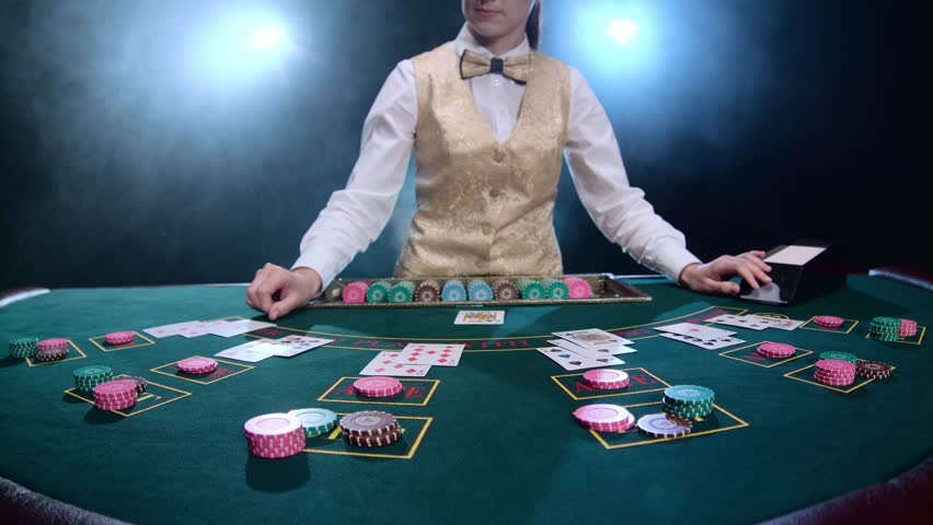 Girl stickman smoothes a complex combination of cards and chips poker game. Smoke. Slow motion