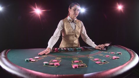 Casino dealer handling playing cards at a poker table. Black background. Slow motion
