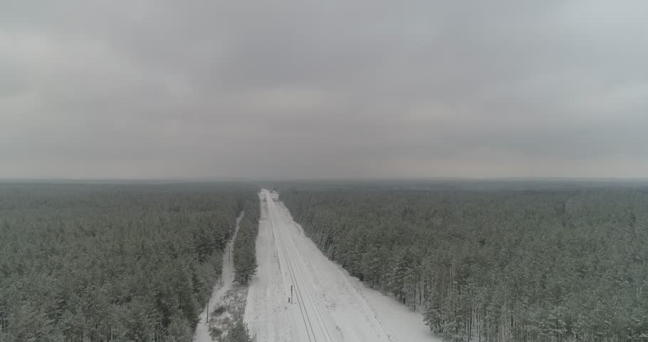 Aerial drone smooth steady footage of winter forest moody sky landscape with railroad track