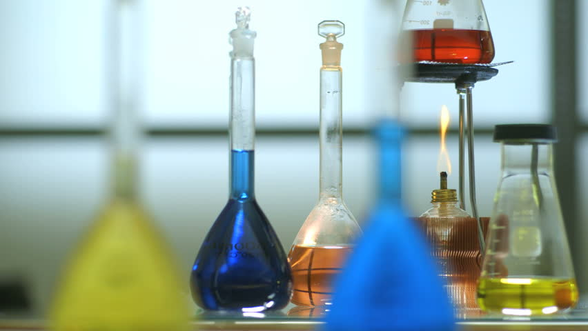 Slight movement to the right across a flame from an alcohol burner and volumetric flasks filled with colorful liquid.