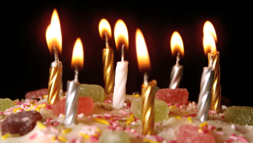 Birthday candles being blown out on a delicious cake close up in slow motion