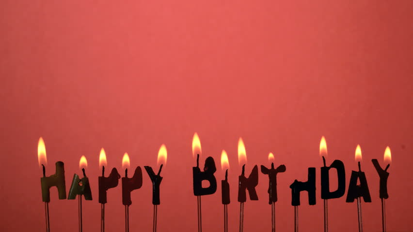 Silhouette of happy birthday candles being extinguished in slow motion