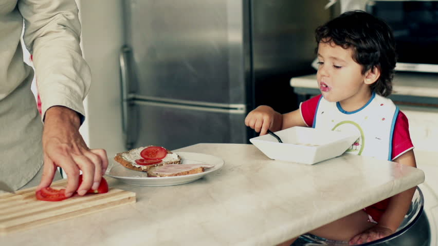 Little boy eating cornflakes with milk, father preparing sandwich, slow motion shot at 240fps