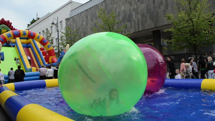 Young girl kids in zorb bubble ball swim in pool basin Vilnius Gediminas prospect on September in Vilnius. Vilnius city capital event.