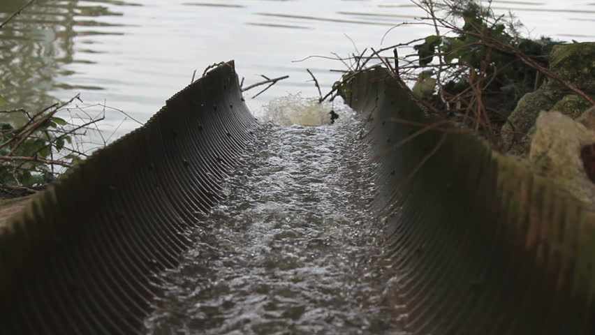 Rainwater funnels through an open culvert and pours into a river/Rainwater in Open Culvert/Rainwater funnels through an open culvert and pours into a river