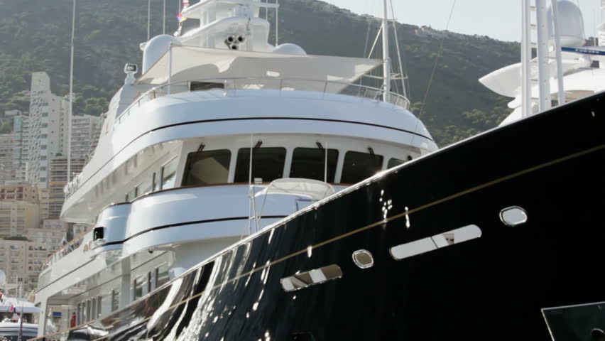 Close up view of Super Yachts moored in Port Hercules, Monaco.  Camera passes ahead of bow of two yachts.