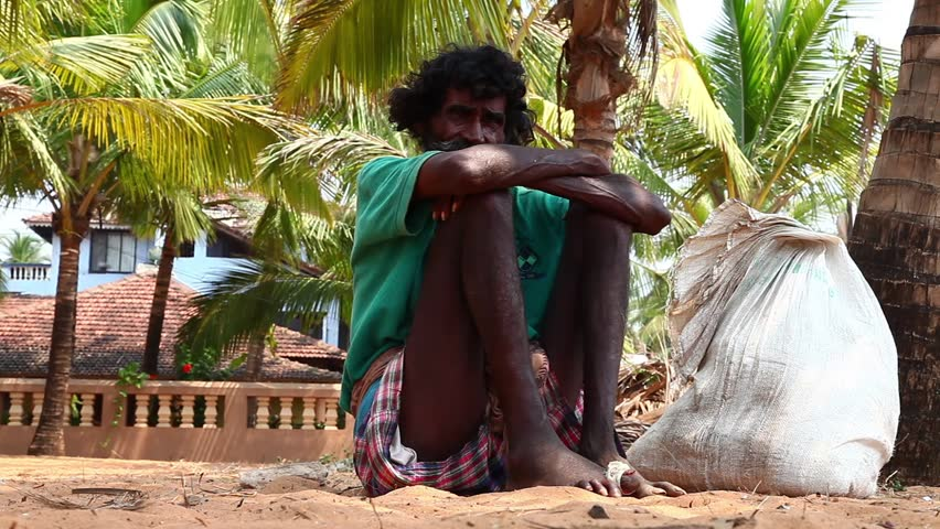 CALANGUTE, INDIA - MARCH 11, 2013: Homeless man sitting on the ground and waiting for alms from passers-by on March 11, 2013 in Calangute, India
